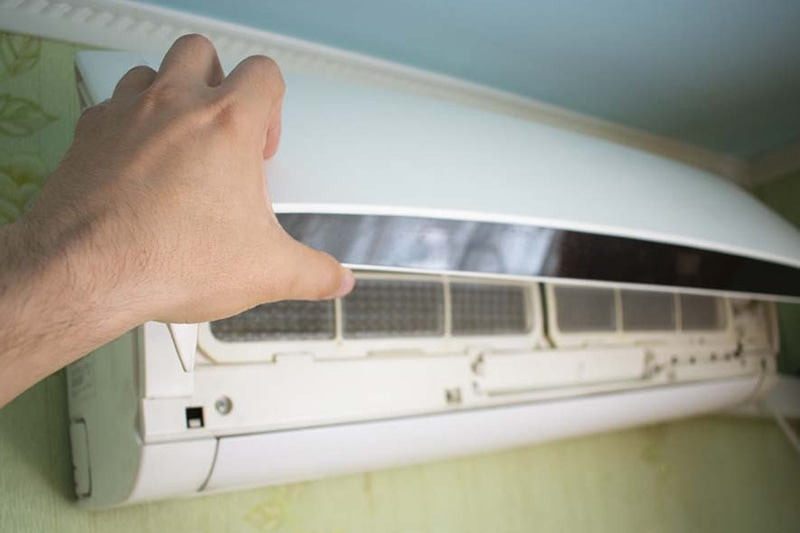Hand open the lid of the air conditioner in the room, Is It Normal for My AC to Turn On and Off? | Short Cycling | York, PA