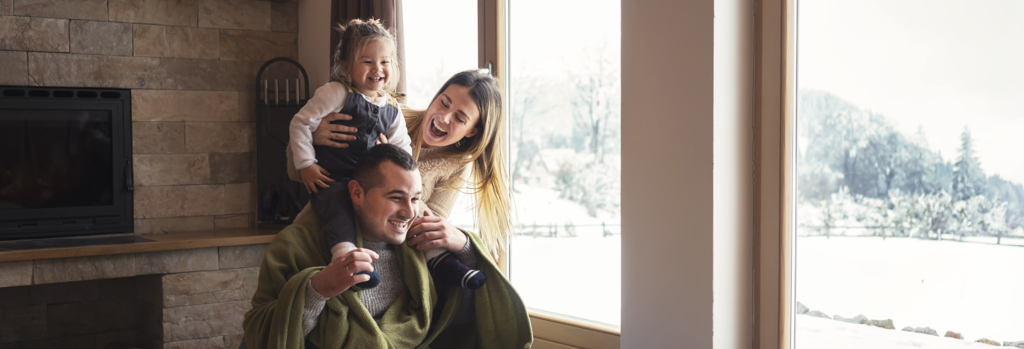 Young family on winter vacation, looking through window