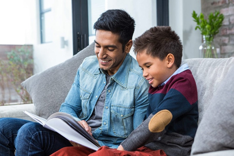 Father & son reading a book on the couch, Prevent Carbon Monoxide Leaks In Your Home | Comfortable Design in PA